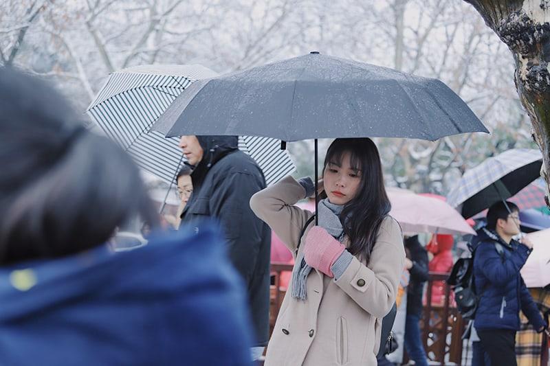 eine traurige Frau, die einen Regenschirm hält, während sie in der Menge steht