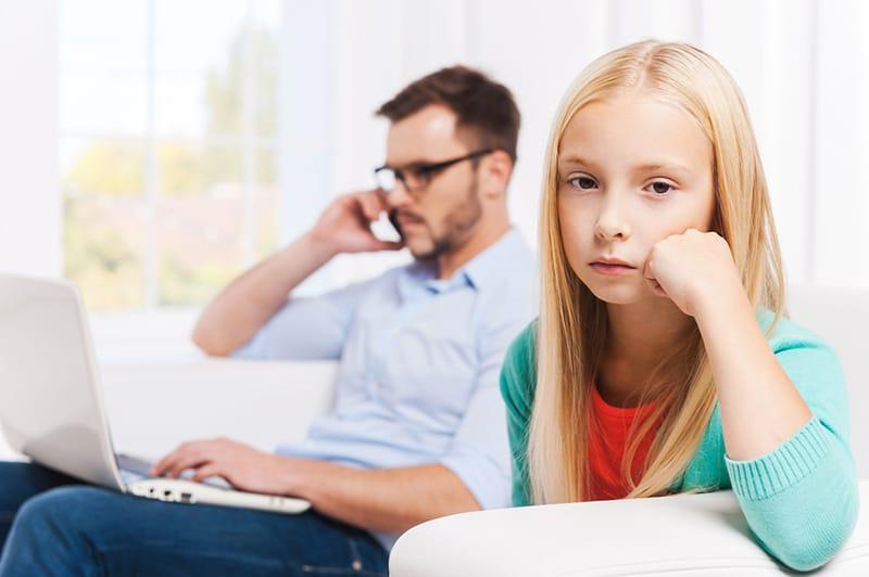 eine traurige kleine Tochter, die auf der Couch sitzt, während ihr Vater neben ihr am Laptop arbeitet