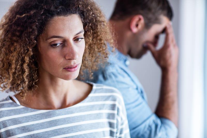 eine unglückliche Frau, die nach unten schaut während Mann mit einer Hand hinter ihr den Kopf berührt