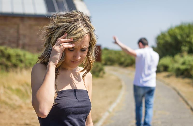 eine unglückliche Frau, die auf dem Weg steht, während ein Mann von ihr geht