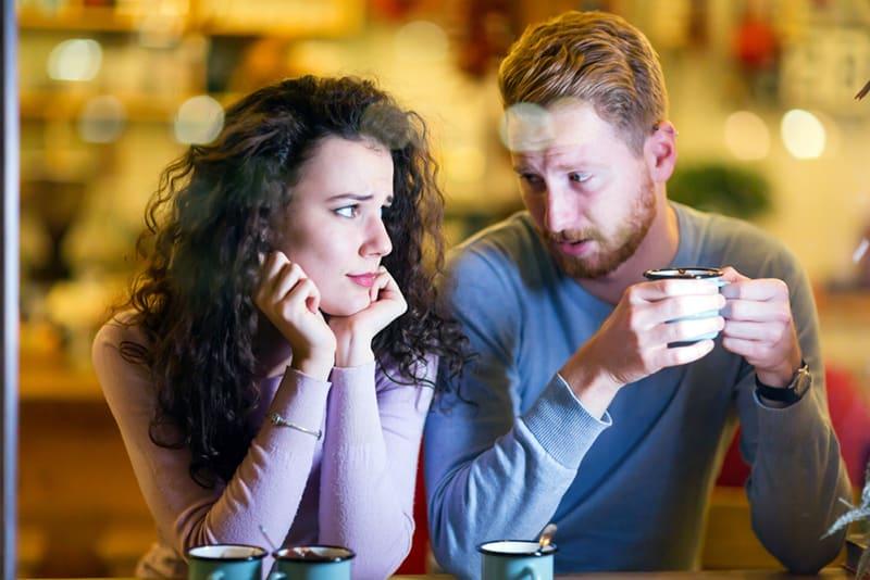 eine verdächtige Frau, die zu einem Mann schaut, der mit ihr im Café spricht