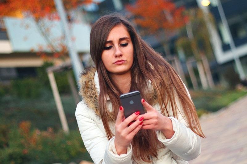 eine verwirrte Frau, die ein Smartphone hält, während sie auf der Straße steht