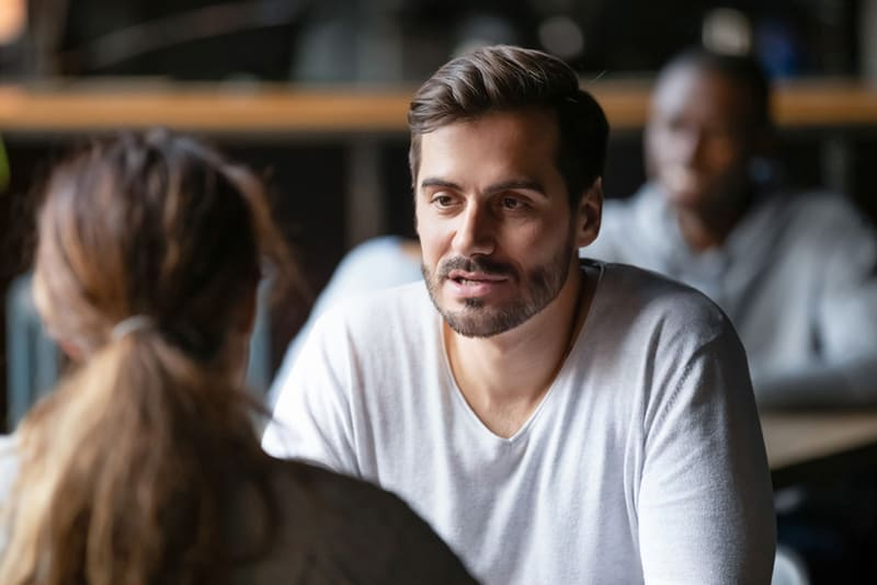 ernsthafter Mann, der Gespräch mit einer Frau hat, während er zusammen im Café sitzt