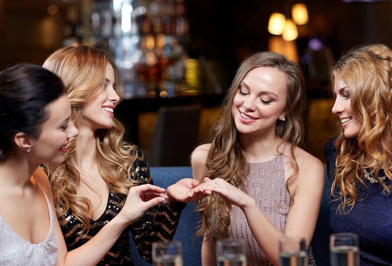 glückliche Frau, die ihren Freunden im Nachtclub Verlobungsring zeigt