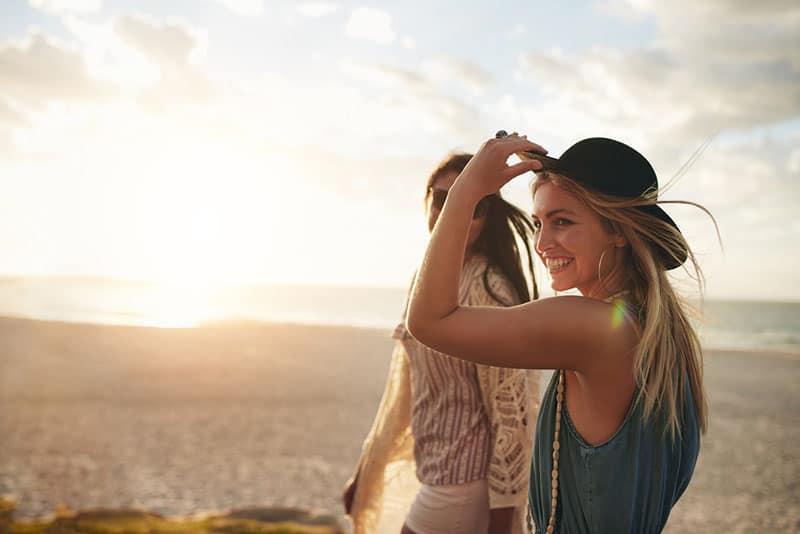 glückliche Frau mit Hut, der mit Freund geht