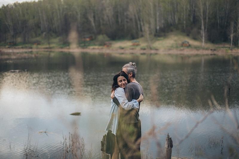 glückliches Paar, das tagsüber nahe dem ruhigen See umarmt
