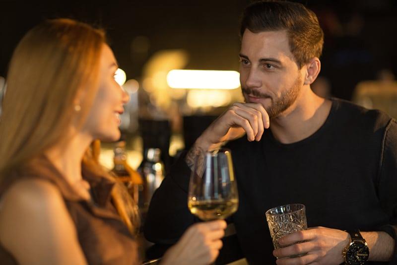 gutaussehender Mann, der nachdenklich lächelt und einer sprechenden Frau zuhört, während er gemeinsam an der Bar Getränke genießt