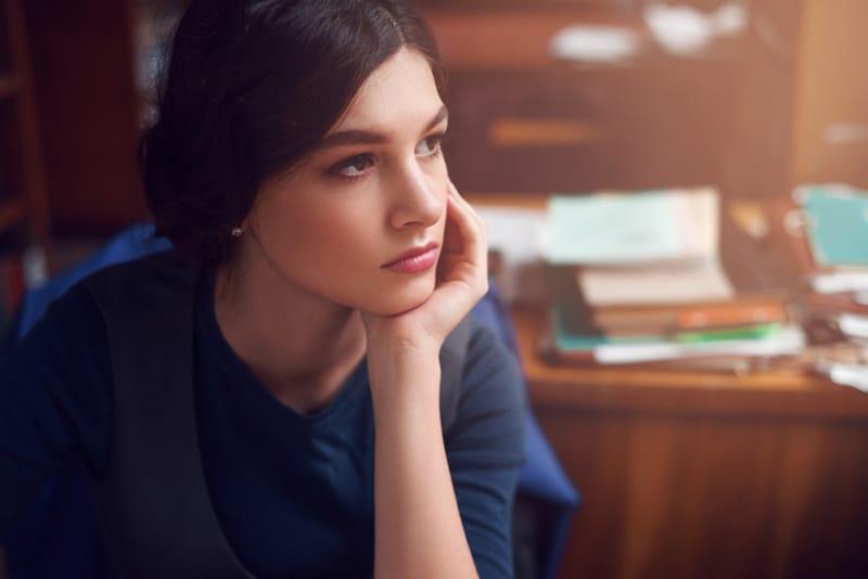 junge Frau, die allein denkt, während sie im Büro sitzt