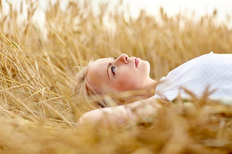 junge Frau, die auf dem Feld liegt und denkt