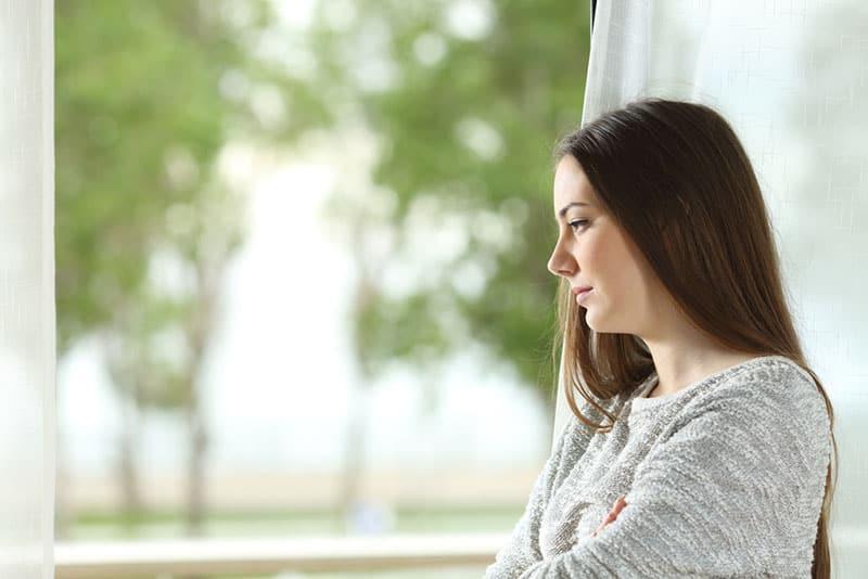 junge ernste Frau, die durch das Fenster schaut