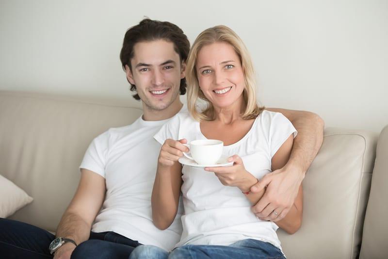 junger hübscher Mann, der attraktive Frau mittleren Alters umarmt, während er auf der Couch sitzt