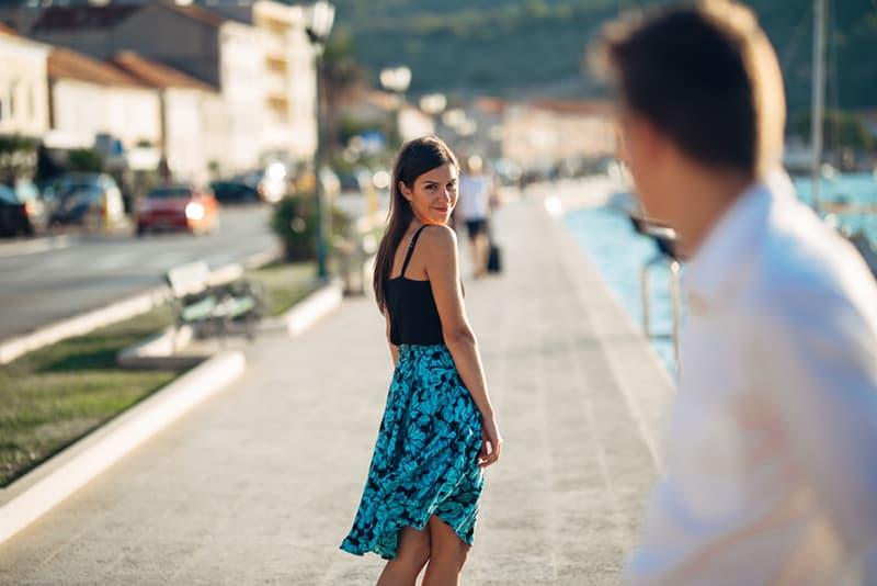 lächelnde Frau, die auf einen gutaussehenden Mann zurückblickt, während sie nahe dem Meer geht