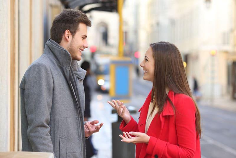 lächelnde Frau, die mit Mann auf der Straße spricht