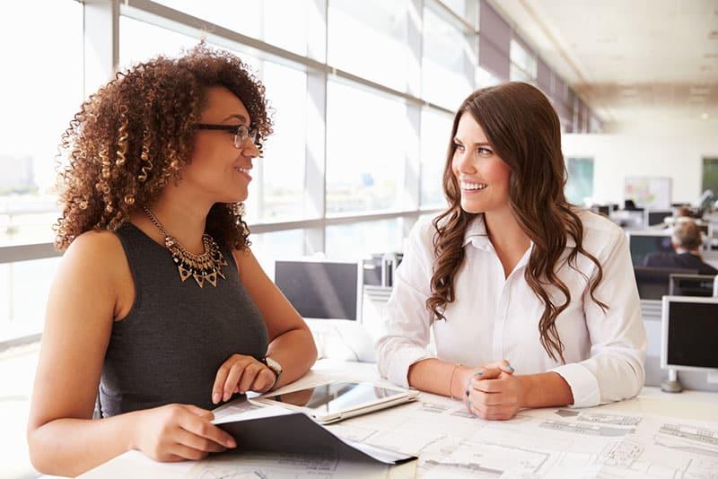 lächelnde Frauen sprechen im Büro