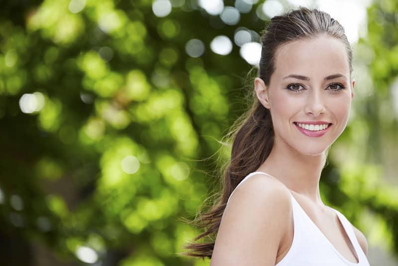 lächelnde selbstbewusste Frau posiert