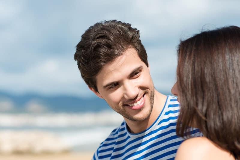 lächelnder Mann, der Frau im Freien betrachtet