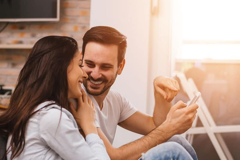 lächelndes Paar, das Handyspiel betrachtet