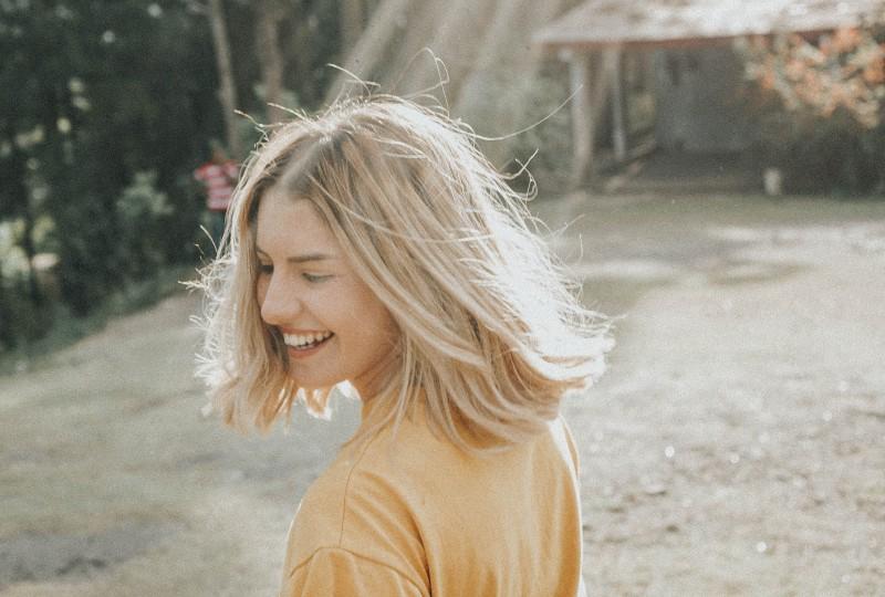 lächelndes schönes Mädchen in der Natur, in der Sonne gebadet