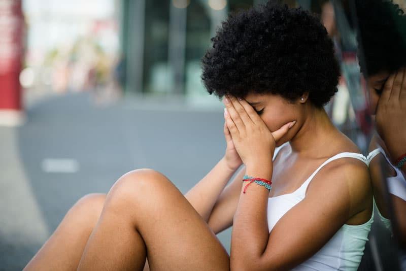 nervöse Frau, die draußen auf dem Boden sitzt