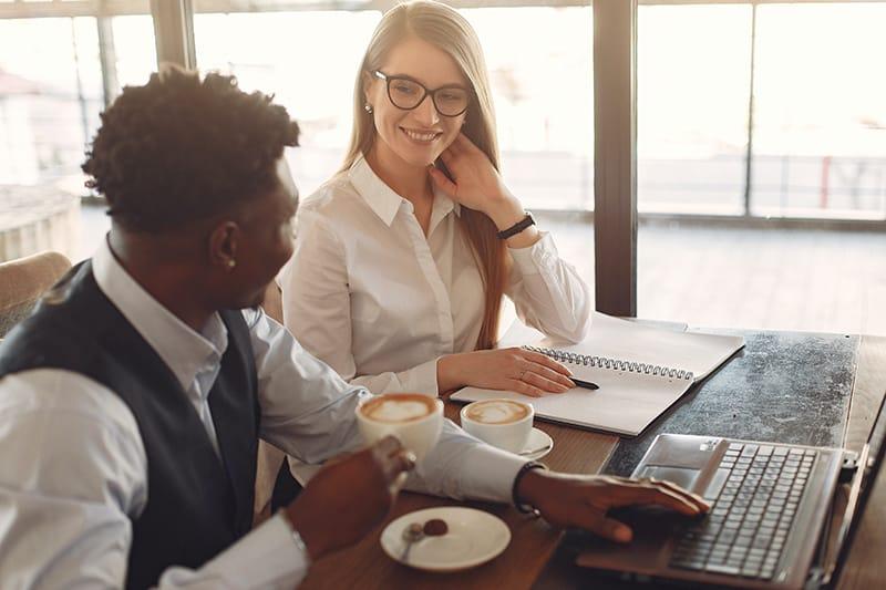 Ein Mann, der einer lächelnden Frau in die Augen schaut, während er gemeinsam am Arbeitsplatz Kaffee trinkt