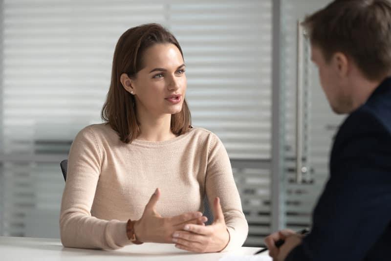 schöne Frau, die mit Mann für Arbeit spricht