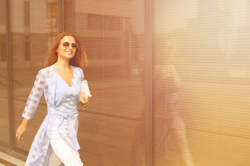 stilvolle lächelnde Frau zu Fuß