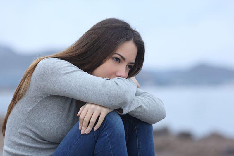 traurige Frau, die am Strand sitzt