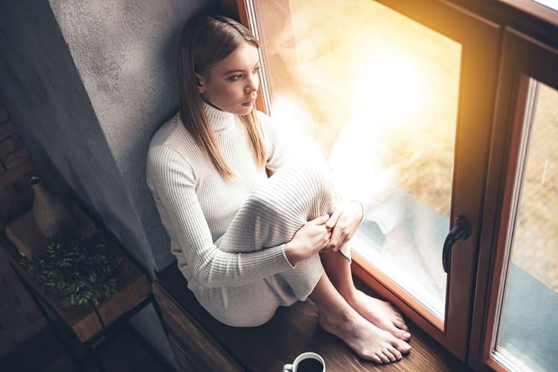 traurige junge Frau, die durch das Fenster schaut