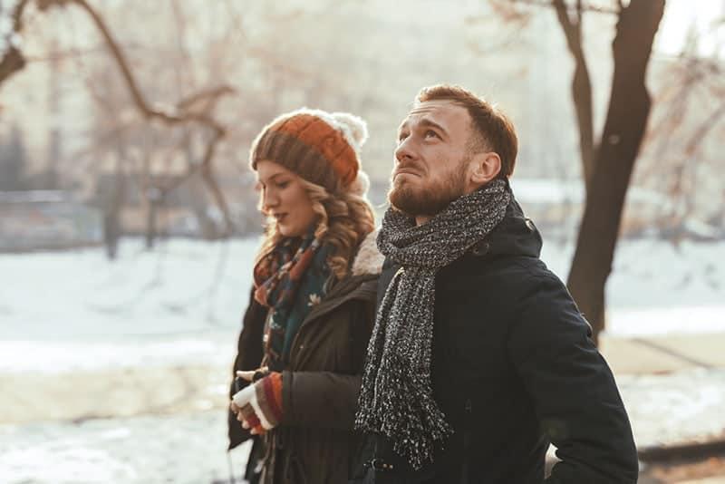 unglückliches Paar, das im Park spazieren geht