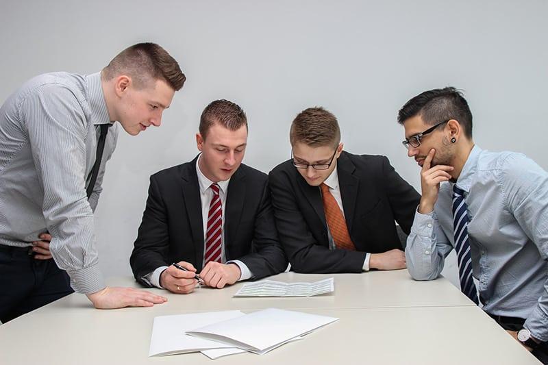 vier Kollegen schauen während des Meetings ein Papier auf den Tisch