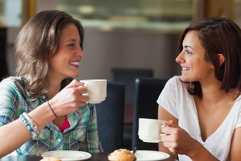 zwei lächelnde weibliche Bekanntschaft, die zusammen Kaffee im Café trinkt