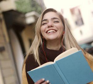 eine lächelnde Frau, die ein Buch liest