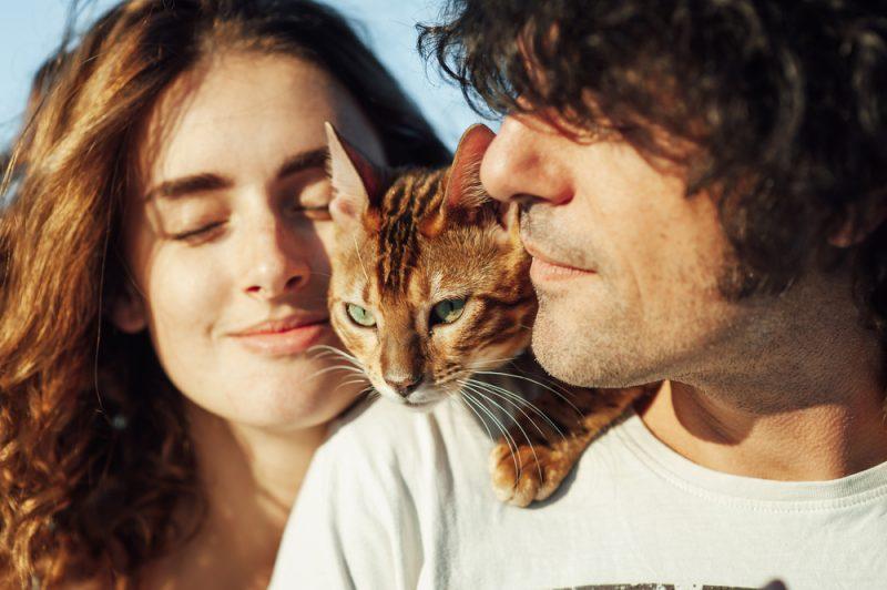 ein Porträt eines Mannes mit einer Katze auf der Schulter und seiner Frau