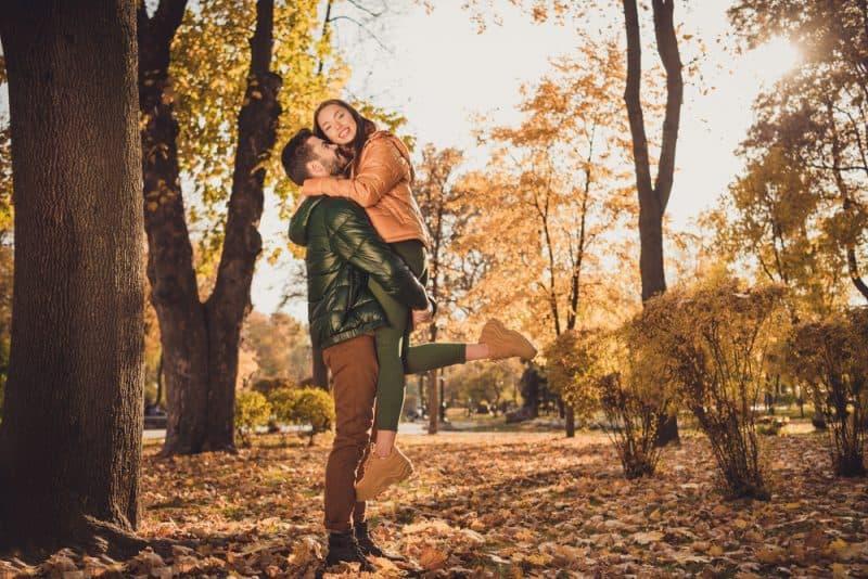 Im Herbst im Park hält ein Mann eine lächelnde Frau in den Armen