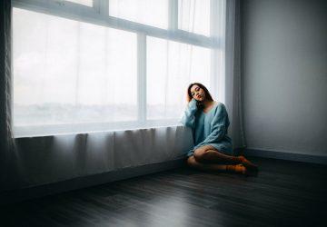 traurige Frau, die auf dem Boden in der Wohnung sitzt