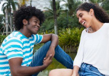 Ein lächelnder Mann und eine lächelnde Frau sitzen und reden