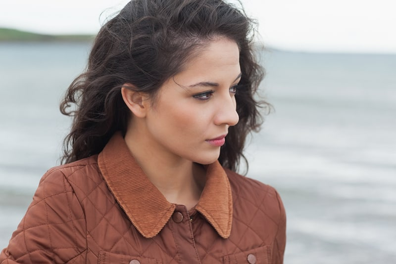 nachdenkliche junge Frau mit braunen Haaren, die am Strand stehen