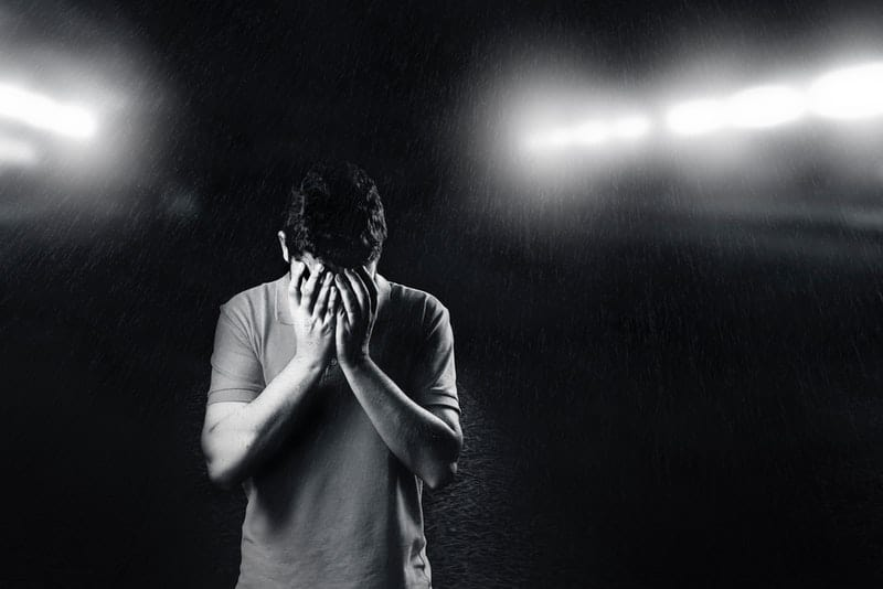 Abends draußen im Regen steht ein trauriger junger Mann