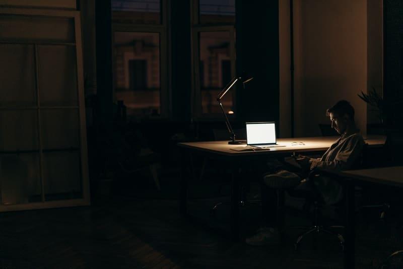 Abends sitzt ein Mann an einem Schreibtisch und benutzt ein Smartphone