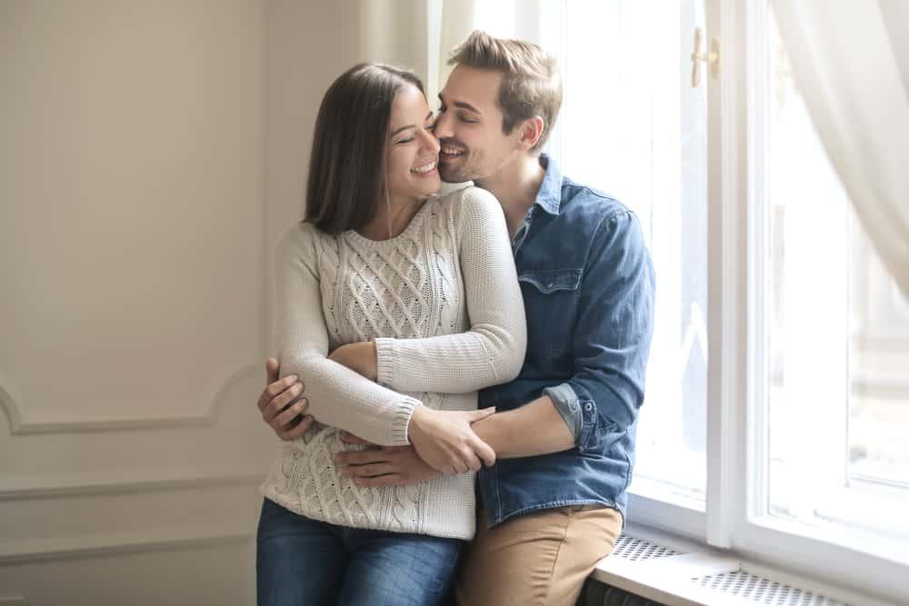 Am Fenster in der Umarmung steht ein liebevolles Paar