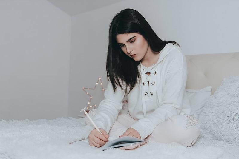 eine Frau sitzt auf dem Bett und schreibt in das Notizbuch