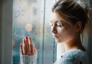 Ein trauriges Mädchen schaut an einem regnerischen Tag aus dem Fenster
