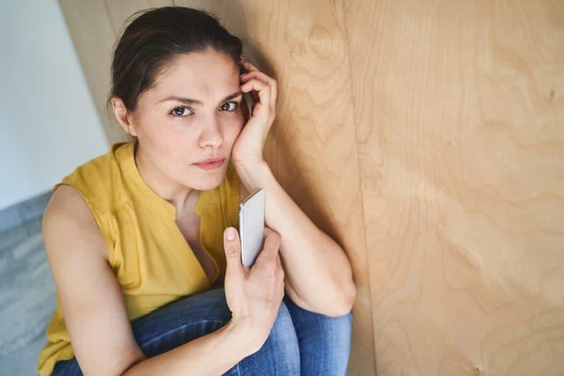 Eine enttäuschte Frau hockt mit einem Handy in der Hand