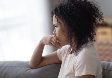junge besorgte Frau, die zu Hause sitzt