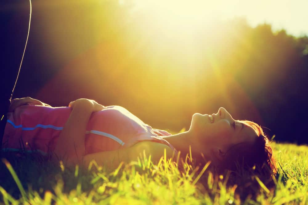 Auf dem Rasen liegt ein lächelndes süßes Mädchen