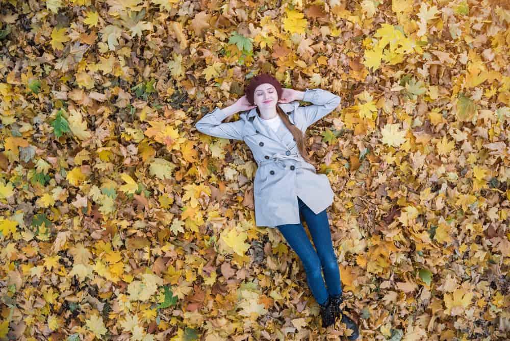 Auf den trockenen Blättern liegt eine junge lächelnde Frau in einem grauen Mantel