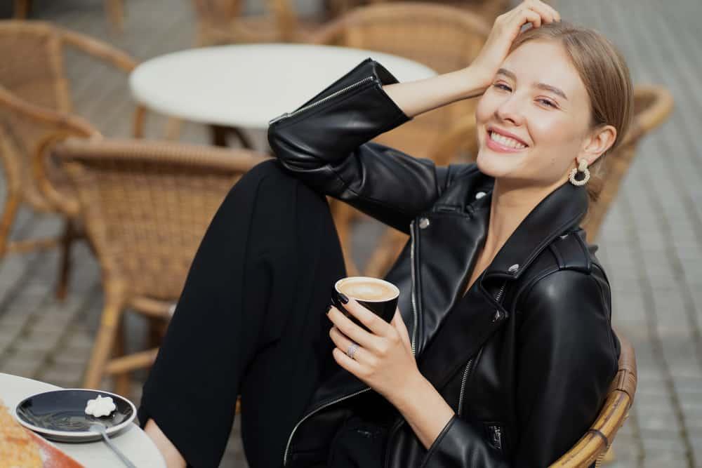 Auf der Terrasse des Cafés trinkt eine zufriedene glückliche Frau einen Cappuccino