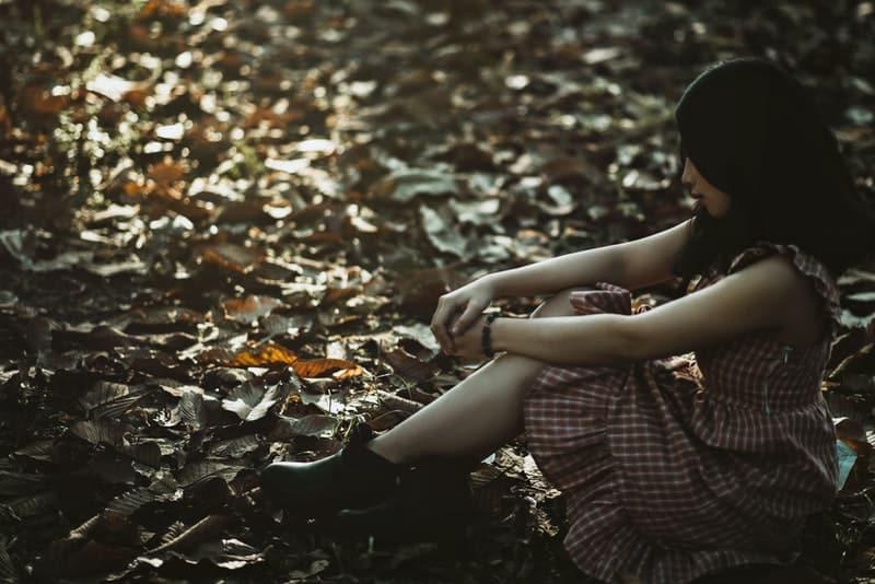 Auf einem trockenen Blatt im Wald sitzt eine traurige Frau in einem Kleid