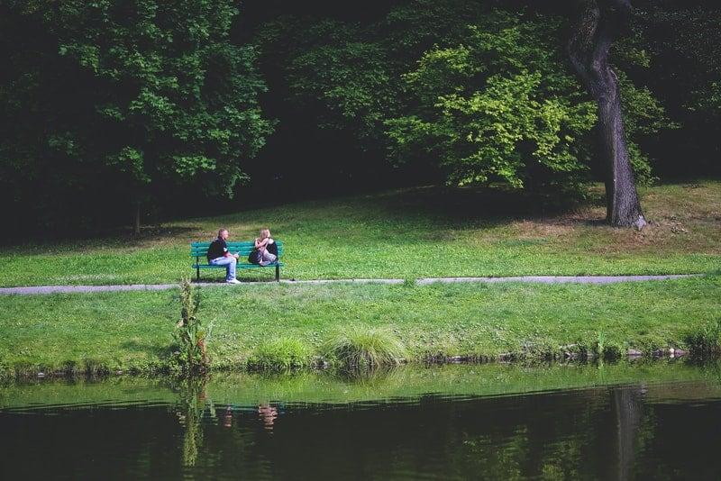 Auf einer grünen Bank am Fluss sitzt ein liebevolles Paar und redet