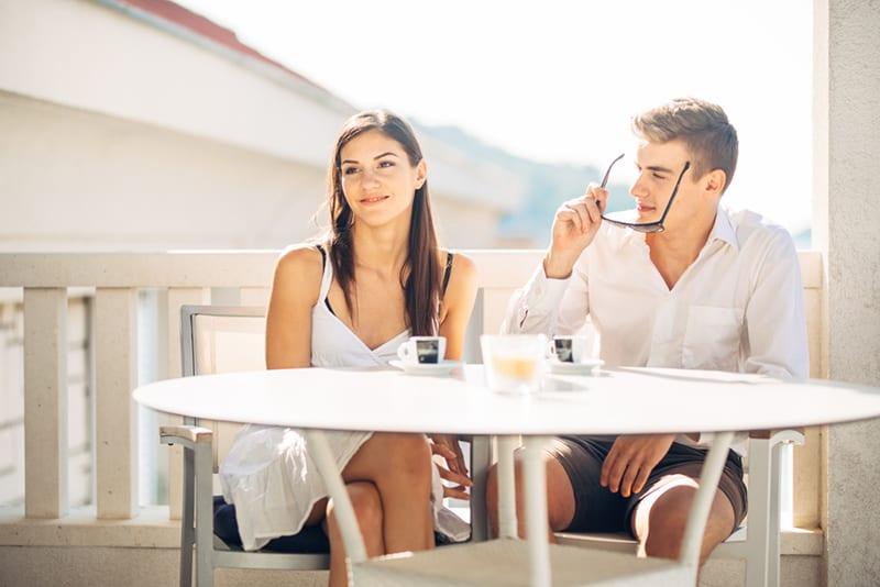 lächelnde nachdenkliche Frau, die beiseite schaut, während im Café mit einem Mann auf einem Datum sitzt